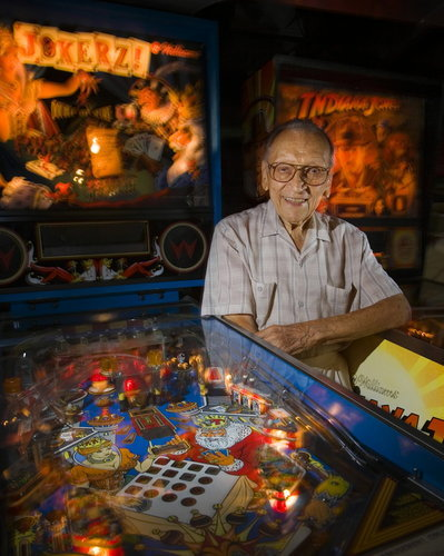 "Steve Kordek, Innovator of Pinball Game, Dies at 100 - NYTimes.com Steve Kordek in the basement of his home in Chicago in 2009.  Steve Kordek, who revolutionized the game of pinball in the 1940s by designing what became the standard two-flipper machine found in bars and penny arcades around the world, died on Sunday at a hospice in Park Ridge, Ill. He was 100. Mr. Kordek actually revised a revision of what until the 1930s had been called the pin game. In that version a player would pull a plunger to release the ball, then shake the table in an often frustrating attempt to redirect the ball toward a scoring target — a cup or a hole. In 1947, two designers at the D. Gottlieb & Company pinball factory in Chicago, Harry Mabs and Wayne Neyens, transformed that rudimentary game into one called Humpty Dumpty, adding six electromechanical flippers, three on each side from the top to the bottom of the field. It was an instant hit — until, at a trade show in Chicago 1948, Mr. Kordek introduced Triple Action, a game that featured just two flippers, both controlled by buttons at the bottom of the table. Mr. Kordek was a designer for Genco, one of more than two dozen pinball manufacturers in Chicago at the time. Not only was Mr. Kordek's two-flipper game less expensive to produce; it also gave players greater control. For someone concentrating on keeping a chrome-plated ball from dropping into the ""drain,"" two flippers, one for each hand, were better than six. ""It really was revolutionary, and pretty much everyone else followed suit,"" David Silverman, executive director of the National Pinball Museum in Baltimore, said in an interview. ""And it's stayed the standard for 60 years…."""