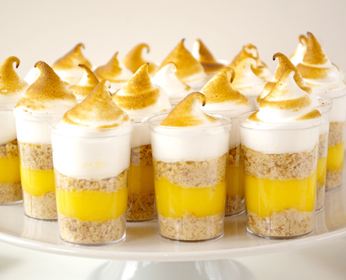 Lemon Meringue Pie Shooters Author: Bria Helgerson Prep time: 10 mins  Cook time: 20 mins  Total time: 30 mins  Serves: Makes about 24 shooters Homemade lemon curd and  italian meringue are two quick and simple components that combine with  store-bought vanilla cookies to make this delicious two-bite dessert. Ingredients Lemon Curd 8 egg yolks 3/4 cup (1,75 dl) sugar 1/2 cup (1,18 dl or 1 stick) unsalted butter, softened zest of 2 lemons 1/2 cup (1,18 dl) lemon juice Italian Meringue 8 oz (227 grams) sugar 2 oz (57 grams) water 4 oz (113 grams) egg whites Assembly 30-35 vanilla wafer cookies, crushed 24 shot glasses (I found these plastic ones at a party supply store) Instructions  Lemon Curd Combine the egg yolks, sugar, butter, lemon zest  and juice in a medium stainless sleet or glass bowl, and set over a  saucepan of barely simmering water. Whisk constantly until lemon curd thickens and reaches 175 degrees F. Remove from heat and let cool, whisking every few minutes to aid cooling. Cover with plastic wrap so the plastic touches  the surface of the curd and chill for a few hours or overnight, the curd  will continue to set up as it chills. This can be made in advance, you can store it in the refrigerator for 1-2 weeks or freeze. Italian Meringue Cook the sugar and water together in a small saucepan over high heat until it comes up to 243 degrees F. When the mixture reaches about 230-235 F, begin  whipping the egg whites in a stand mixer on medium-low speed until they  are foamy. When the sugar reaches 243 degrees F, remove from heat, and pour very slowly in a steady stream into the whipping egg whites. As soon as all the sugar is incorporated, turn the mixer onto high, and whip until completely cool. Assembly Place a small amount of crushed cookie into the bottom of each shot glass. Transfer your lemon curd to a pastry bag and pipe a small amount into each glass. Top each glass with more crushed cookies. Transfer your meringue into a pastry bag fitted with a large plain tip and pipe a big dollop on top of each shot glass. Using a kitchen torch, carefully toast each  meringue top until they are golden brown. If you are using plastic shot  glasses, be mindful just to toast the tops of the meringues, otherwise  you run the risk of melting the plastic. Refrigerate until ready to serve.