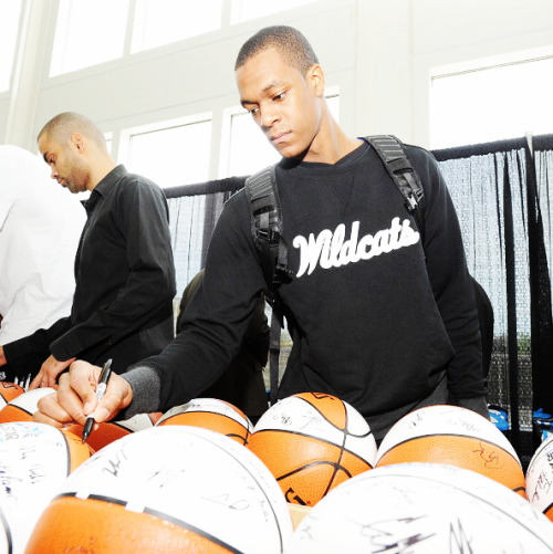 Rajon Rondo signs some basketballs.