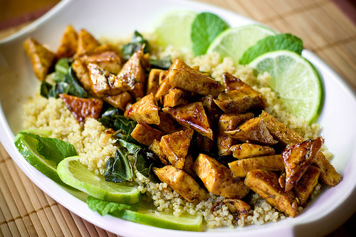 "Sweet Chili Lime Tofu with Wok Steamed Collards and Quinoa from veganyumyum.com. check it out, great recipes! Serves 2-3 1 Block Tofu, extra firm, 14 oz Sweet Chili Lime Sauce3 Tbs Sugar3 Tbs Reduced Sodium Tamari (or soy sauce)1 3/4 Tbs Fresh Lime Juice1/2 Zest of the Lime1/2 tsp Red Chili Flakes (or 1-2 fresh hot chilies, minced)1 Clove Garlic, pressed, optional1/4 tsp Salt4 Mint Leaves, chiffonaded Quinoa*3/4 Cup Quinoa, rubbed/rinsed in cool water, drained1/2 Zest Lime2 Bruised Cardamom Pods, optional1 Tiny Stick of Cinnamon (a broken piece of a larger stick), optional1/4 tsp Salt1 1/3 Cup Water *Other options: For brown rice, adjust water to 1 1/2 cups, for medium/long grain rice, water measurement is the same. Noodles can be boiled, drained, and given a light splash of soy sauce and lime juice for some background flavor. The tofu is very flavorful, so whatever base you choose, it needs only subtle additions, if any at all. Wok Steamed Collards1 Bunch Collard Greens, middle veins removed, washed2-3 Tbs Water1 Pinch Salt1 tsp Lime Juice Directions  Combine all the ingredients for the quinoa in a pot that has a tight fitting lid. Bring to a boil, then cover and reduce heat to low. Cook for 20 minutes, then turn off heat. Do not open lid. Let steam for 10 minutes before serving. Prepare the sweet chili lime sauce by whisking all of the ingredients together until the sugar and salt is dissolved. Drain tofu and cut it into small triangles. I slice the block into 8 rectangles, then each rectangle in half to make two squares per rectangle. I cut each square diagonally to make four triangles per square. Tofu geometry is my favorite kind of math! You can cut the tofu however you please, but a thinner, smaller shape will work best for this method. Heat a well-seasoned cast iron or non-stick skillet over medium heat. A 10″ skillet will fit all the tofu, so if you're using a smaller skillet, you'll need to do this in batches. In order to properly ""dry fry"" the tofu, you'll need a pan the tofu won't stick to even without any oil. Spread the tofu out in one layer in the pan. Using a spatula, press the tofu. The liquid will squeeze out and boil away, and the tofu will begin to turn golden. The more water that evaporates, the sturdier the tofu will be, so be gentle at first to prevent the tofu from breaking up. After several minutes, flip the tofu over and press the other side. After about 10 minutes of dry frying, you can turn off the heat and set the tofu aside for finishing later, or proceed to adding the sauce. (You might want to set the tofu aside before finishing in order to to prepare the collards, below.) To finish the tofu, bring the pan back up to temperature if it's not already very hot. You want to heat the pan and the tofu over high heat, making sure the tofu is hot all the way through. Add the sauce and stir to coat the tofu. Turn off the heat. The sauce will bubble up, reduce, and form a glaze. If it isn't bubbling up and forming a glaze, turn the heat back on high and cook until the glaze is.. well.. glaze-y. Stack the collard leaves on top of each other, 3-4 at a time, and roll. Slice the roll in 3/4 inch segments. Run your knife through the chopped collards to make smaller pieces, then add them to a wok with the water, lime juice and salt. Cover with any lid that will contain the collards and cook over high heat for 3-4 minutes until the collards are steamed and tender. For plating, arrange the collards atop of a bed of quinoa. Add tofu over the top, drizzling any leftover sauce over the dish. Garnish with lime slices and mint leaves. Serve."