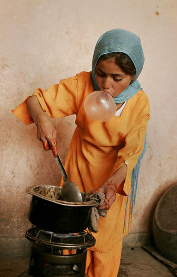 delucazade:  An Afghan girl blows bubblegum while she cooks food for her family in Kabul, Afghanistan. Farzana Wahidy