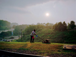 "Pittsburgh (Man cutting grass), 2004 from ""a shimmer of possibility "" © Paul Graham/steidlMACK ""This picture is actually part of a sequence of photographs I took on the first evening of a two-and-a-half-year trip around America, starting in Pittsburgh in 2004. I was just travelling with no particular purpose, taking photos along the way. This was in the car park in front of the motel where I was staying, and there was this guy cutting the grass of an entire huge field with a very loud old push-mower. A ""great shot"" is the antithesis of what this work is about. It's about appreciating the flow of the moment, the rhythm and currents and eddies of life, rather than neatly packaging the world into perfectly formed little jewels. He saw me and lifted his hand at one point, but he didn't really care. So I kept on taking pictures, with the sun shining directly into the camera. (It's lovely to do everything that Kodak tell you not to.) In one image from this sequence, he is to the left, then he's to the right, then he's wiping his face with a cloth. Then this beautiful moment happened: the sun burst through and the rain came down, and all the raindrops were illuminated in the shaft of light. It was quite extraordinary. I like this shot because, besides the obvious reason of its beauty, it confers a nobility on what the man is doing. He was working with dignity on this unbelievable task - and, with perseverance, he was probably going to get it done. Many moments are mundane and seem worthless, but they form and shape our lives. They are quite different from the Herculean labours and extraordinary moments that photographers are addicted to."" - Paul Graham (Paul Graham's best shot on the guardian)"