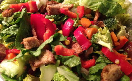 Colorful Salad with Homemade Herbed Croutons You know how when you go to buffets or dining halls or salad bars the salads are always SO good? There are so many choices and textures and flavors. There are croutons and veggies and fruits and seeds and peas and dressing and it's all so crunchy and wonderful. When I moved off my college campus and away from those salad bars, I decided it was time to take matters into my own hands and create a salad just as exciting and versatile.  I have figured out that they key components to creating a successful salad are: croutons, good dressing, lots of colors, and small juicy items like peas or corn. I prefer making my own croutons to buying them (cheaper, healthier, more fun). I save the ends of bread (yeah, I don't eat the ends, so what) and freeze them. When salad time rolls around I pop them in the microwave, chop them up and sautee them til they are crispy and greasy and delicious. In terms of dressing, I love tahini dressing or sesame-soy-ginger, but an easy and still yummy way to go is olive oil and balsamic vinegar, or lemon juice, salt and pepper, or all of the above.  I made this salad with my wonderful best friend, A. She is just getting into cooking and it's so much fun to teach her what I know and watch her get excited as she invents new and delicious meals.  You can really put in almost any vegetable and your salad will taste great, but here's what we did: Ingredients: Romaine lettuce, washed and chopped Frozen peas, cooked and let to cool Canned corn, drained Broccoli (raw, or slightly steamed) Bell pepper  Carrots Celery Several pieces bread Olive oil Salt, pepper, garlic powder, rosemary and thyme Dressing Directions: Defrost bread if necessary, cut into crouton size pieces Heat olive oil in a pan, add bread and mix around so all the pieces get oily Add herbs and oil as needed (it takes a bit of oil to get them crispy) Sautee until croutons are crispy and flavorful (this tends to take at least 10 minutes) Meanwhile, wash and chop veggies into bite size pieces Mix veggies and croutons together in a large bowl, add dressing and toss Serve and enjoy -N