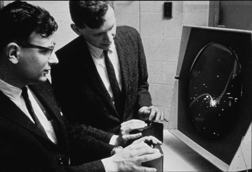 "A couple of regular dudes playing ""Spacewar!"" on the DEC PDP-1."