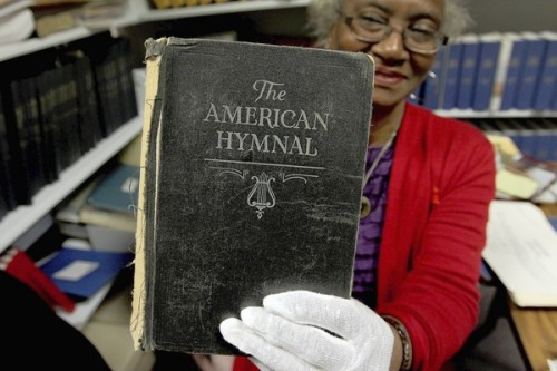 latimes:  Historic black church rises from ashes of Civil War: The legacy of First Baptist Church in Hampton, Virginia — founded by free and enslaved blacks on the site of a place abandoned and burned by rebellious whites — can still be felt nearly 150 years later. Photo:   Church archivist Catherine Howard holds up a hymnal that dates to the founding of First Baptist Church Hampton after the Civil War. Credit: Rob Ostermaier / Daily Press