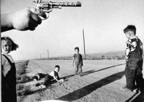 "Howard Sochurek, Chubby boy's hand holding toy six-shooter over two young boys lying in a country dirt road, giggling over their make-believe bullet wounds while two others walk in to survey the damage during a game of ""cops and robbers"", Kansas, USA, 1952."