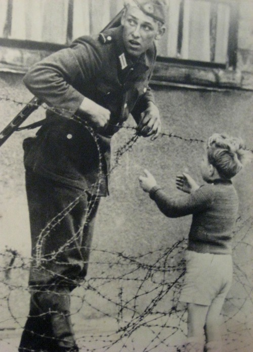 ausschreitungen:  A soldier helping a boy over the barbed wire. After the picture, the soldier was immediately replaced. God only knows what happened to him afterwards.