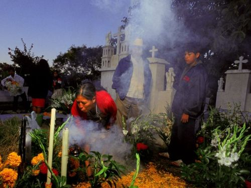 the-native-soul:  Day of the Dead, Puebla, Mexico Photograph by Russell Gordon, Aurora Photos There are better-known Día de los Muertos celebrations in Mexico, but spending the extended holiday (October 31-November 2) in the Puebla state capital puts you in close proximity to the elaborate Day of the Dead ofrendas (offerings) in tiny Huaquechula. Families here spend thousands of dollars erecting towering, multistory altars (typically a cardboard foundation draped in satin) adorned with wax candles, a photo of the deceased, and a sampling of his or her favorite food and drink. Hire a local guide in Puebla to make the bumpy, 35-mile ride west, and then follow the trails of marigold petals to homes where guests are welcome to pay their respects (and, perhaps, share a tequila toast to the dearly departed). Bring along a few coins or a sugar calavera, or skull—available from village vendors—to place on the ofrenda table. Back in Puebla, head to the Casa de la Cultura to view the indigenous and modern altar-building contest entries and visit with the artists. Pictured here: Family members visit the graves of relatives on the Day of the Dead in Huaquechula, Puebla, Mexico.