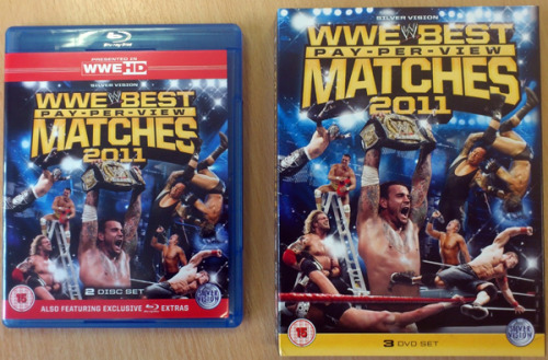 It's not often that the DVD and Blu-ray come into stock at the same time, but that's exactly what just happened with WWE Best PPV Matches 2011 - so if you ordered it it is on its way, and may even be with you already! For those that haven't, here's a closer look at the packaging.  No surprises that Money in the Bank 2011 is the main feature on the back cover as many would say it was the best WWE PPV of 2011.  The reverse side of the Blu-ray cover lists the contents. Here's a question for you - can you name which match and PPV the images on the discs are from? Here's the inside of the DVD set so you can see Disc 2 which has a different image and you have a another match to guess.   Here is another photo of the inside of the DVD set:  My favourite PPV poster from 2011 is definitely SummerSlam, but I also liked Royal Rumble - what about you?  No prizes for guessing the match on the back of the DVD set - that one is obviously from WrestleMania 27. I can't wait to see their re-match at WrestleMania 28 - I wonder if Triple will be the one to finally break Undertaker's streak, or will we see the Phenom make it 20-0? You'll be pleased to know that the DVD does come with an insert listing the contents of the set, and here it is:  So there is your guided your of the WWE Best PPV Matches 2011 - I hope you enjoy watching it, and who is up for the disc match challenge that I set earlier?