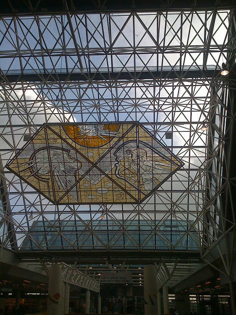 "stained glass at keflavik on Flickr. This is the ceiling of the airport in Keflavik.  Last year on the last day of February I was returning to America by airplane.  It had been a very long journey, and I was looking forward to returning to my home, my lover, and to my dog. In preparation for the trip I had read only one book about explorers, which was about the guys that got stuck in the sea off greenland. In it I learned that without the natives, particularly without a lady Inuit named Tookoolito, the explorers would have died. Even with the natives, they were up to some dumb stuff in the name of adventure. Is this the story with all adventurers? Maybe.   Back in Norway, earlier on the trip, while we were devouring the best meal we ate in the coldest tent ever, [somewhere in the wilderness (in the neighborhood of where? We traveled 46 miles by dogsled. (South of Finse, North of Oslo)] our guide described being on Greenland and staring up at airplanes flying over him and imagining the residents of those planes eating the meal he was preparing for us. If I said this was the only time I liked him, it would be a half-truth, but it was a moment when I felt like he had dropped a little of the macho ego that made the portion of the voyage with him sort of reckless and dangerous and barely tolerable.  I like it when we remember we are small drops in a big freaking universe and here he was, admitting it, and talking about the foods he fantasized about while he himself was forcing himself to eat the 4 staples of the Amundsen expeditioners. I can't remember if this was the same night that the camp stove was filling the tent with noxious fumes or not.  On the flight home, we flew over Greenland and Newfoundland and I peered down on the continents, and I felt small and alive. On the tv there was a really not very excellent movie, a sequel called ""Wall Street: Money never sleeps"" but what is important about this film was that the soundtrack was songs from the David Byrne & Brian Eno collaboration record, ""Everything that happens will happen today."" I would argue that David Byrne really knows how to write songs about home. There was this song: http://www.youtube.com/watch?v=dYYU1mJSeOs and there was a lot of images of New York, where we would fly into in a few hours. I never really think of Manhattan as my home, unless I am far from home and trying to describe what I am near. I am near Manhattan. When I first went to college on the West Coast I would encounter people who had never been to Manhattan and think I was really awesome because I was only a train ride away from there. ""You've never been to NY!?"" I'd say, as though this was some thing that we all must do if we want to be sophisticated 19 year olds. Goodness, what an ass I was.  The music was from a record I had listened to a great deal in the year and a half before the trip, the record helped to ground me in my place in the world, and I had seen D.Byrne perform the music at the close of 2008.  And back on earth, will all my fingers and toes, a year later. Holy Moses that was an adventure.  I remember feeling a little out of the travelling league with all the Europeans talking about all the continents they had visited and when they asked me about myself I mumbled something about liking to travel in America. Because I do. This is a land that I have a lot of complicated feelings about but damn if it doesn't contain multitudes. A person could spend a lifetime exploring their backyard. I am glad to be an explorer of my backyard and I am glad for adventures that remind us again that where we live is a beautiful place indeed.  Last night I rode my bike back from ballet class and I took the road that slides along the harbor and I watched the sky and the stars and I was grateful for what a year can be, and do. It was an adventure that made me appreciate the comforts of comforts. Amen"