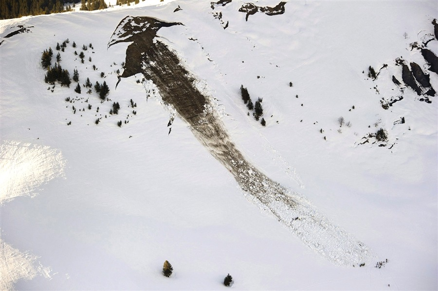 An aerial view shows rescuers searching for persons under an avalanche at Col de la Croix in the Skiing area on Wednesday, Feb. 29. It is assumed that two persons are buried under the snow. Picture taken out of a rescue helicopter shows people searching for victims after an avalanche near Col de la Croix mountain, Swiss Alps, near Les Diablerets, Switzerland.  [Credit : Jean-Christophe Bott / EPA]