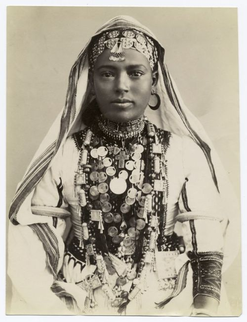 Girl in ceremonial dress Egypt, Syria  (NYPL Digital Gallery) They have labelled the lady in the photo from Egypt or Syria but her dress, her cross, her features and the rest of her jewellery say Eritrea/Ethiopia.