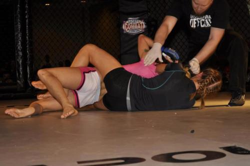 Here's a picture of my fight. That's me in the gray/black finishing the submission (with the referee separating us). I don't know who wants to see an unposed picture of MMA female fighters, but I figure someone out there does. The posed ones usually aren't accurate of what happens in the cage.