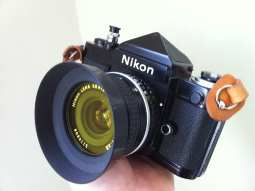 Black Nikon F2 - 1978 vintage. Black DE-1 Eye Level Finder - Standard non-metered prism. Had an unexplainable outward facing ding. Tried fixing it, now it has an outward/inward facing ding. Nikon 28mm F2.8 Series E Lens with Yellow Filter - This is smaller than the Nikkor version. Nikon AR-4 Soft Release - Looks like a chimney. People pay big bucks for this thing. Not sure why. Maybe because it makes you feel cool.