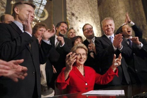 Supporters applaud Monday as Gov. Chris Gregoire lifts her hands after signing legislation to legalize gay marriage in Washington state.