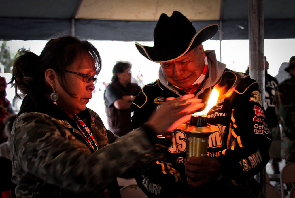 "A Navajo Gold Star family receiving the strength and warmth of the ceremonial torch as they remember their lost one during the 9th annual Navajo-Hopi Honor Run's torch ceremony. The ceremonial torch is from ""Carry the Flame Across America,"" a non-profit organization that is dedicated to the honor and memory of Veterans.  Related Video: http://www.youtube.com/watch?v=51PH6xX0rAI"