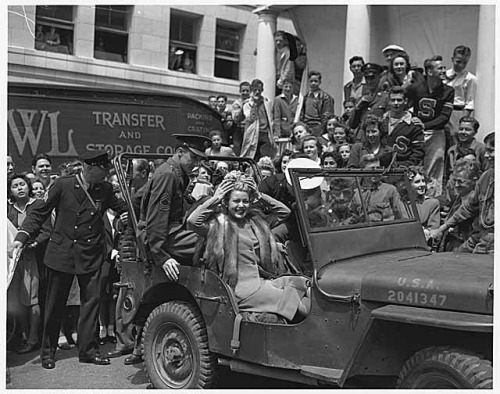 Lana Turner in Victory Square, Seattle, June 15, 1942 Lana Turner, one of Hollywood's most popular stars, visited Seattle on June 15, 1942, to help sell war bonds. She autographed bond receipts at Victory Square, attended a benefit dance at the Trianon Ballroom and sold bonds at I. Magnin's department store. Ms. Turner promised to kiss anyone who bought a $25, 000 bond at the Star Spangled Bond Rally at the Civic Auditorium that evening. In this June 15, 1942 photo, Lana Turner has just arrived at Seattle's Victory Square in a jeep. The popular movie star attracted the largest crowds seen in the square to that date. Victory Square was located on University Street between Fourth and Fifth Avenues. Photographer: Seattle Post-Intelligencer Staff Photographer Image Date: June 15, 1942 Image Number: PI28253 To order a reproduction or to inquire about permissions contact us on our website or phone us at 206-324-1126. Please refer to the Image Number and provide a brief description of the photograph. Original Article