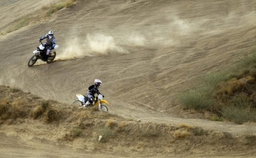 Noora (R) and Shahrzad Naraghi practice on a motorcross track in the mountains overlooking Tehran July 3, 2011. Shahrzad Naraghi started riding motocross eight years ago to spend more time with her daughter Noora who became interested in the sport after watching her father compete in races, and began riding motorcycles at the age of four. The pair raced against each other at first and in women's only motocross races in Iran in 2009. In 2010, Noora travelled to the United States, completed training courses and raced in competitions sponsored by the American Motorcyclist Association. Women are banned from driving motorcycles on the streets of Iran. Picture taken July 3, 2011. (via Photo from Reuters Pictures)
