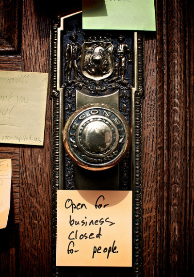 "1 year ago. Post-it note at a locked-down Wisconsin Capitol building. ""Open for business. Closed for people."""