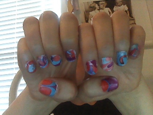 Marbleized Nail Designs Materials: Room temperature water in a cup Toothpicks Scotch tape Nail polish remover Q-tips Clear polish (or gel kit) White nail polish Your favorite nail polish colors  Procedure: Either do the first steps of gel kits (buff, alcohol, ph bond, foundation, top it off) or use a clear base coat. After this DRIES, do a coat of white (I did this with my gel kit as well, so after I used the UV light, I did another coat of top-it-off & UV-light again). After that dries, do another coat if necessary. Put pieces of scotch tape around your cuticle to make cleanup easier. Now take the cup of water and drop ONE drop of new nail polish into the water. (Drop one of whatever colors you want to use.) Before the polish dries, use the toothpick to create a design. Dip your nail into the polish. While nail is underwater, blow on the top of the water for about 10-15 seconds. Use the toothpick to spin the excess polish off of the top of the water. remove finger from water. Repeat 5-10 for each nail. Remove scotch tape. When fingers are dry (which shouldn't take long), do another clear coat (I did another coat of top-it-off under the UV-light). Tah-dah!