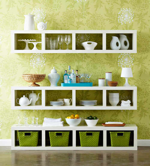 "Better Homes & Gardens | Bookshelf Dining Display China cabinets and wooden hutches are all well and good, but bookshelves can do the job even better! China cabinets and hutches can be beautiful and ornate, but are typically old fashioned and super expensive, not to mention they take up a lot space, can rattle around on uneven floors, and are really heavy if you move or rearrange a lot. Instead of having to deal with all of that, purchase some simple bookshelves and design your own china ""cabinet"" on the wall! For this particular display, 3 tall white bookshelves were used. Flip the shelves on their sides and hang one at countertop level, another at cabinet level, and slide the last one on the floor beneath. The bookshelves are long and thin, taking up minimal space and allowing the room to breathe. Not only can you utilize the openings of the bookshelves, you can also use the tops as shelves to hold your vases, dishes, table linens, and knickknacks. Paint the book shelves to match your décor if you can't find any you like and make sure you hang them sturdy on the walls before adding heavy items."