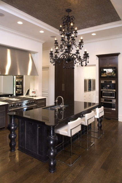 Classy kitchen with simple lines offset by a fancy black chandelier (via John Kraemer & Sons)