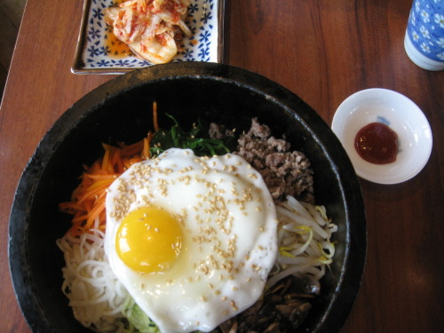 "Bibimbap  Above is a most delicious dish called ""Bibimbap"" that I ordered from Taka Japanese and Korean restaurant several weeks ago (I've been a guilt-ridden blogger for not posting earlier).  The ingredients are deceptively deconstructed, being egg, sesame seeds, rice, shredded turnip, carrot, spinach, ground beef, bean sprouts, mushrooms and cucumber.  The magic of this dish is the heated stone bowl it is served in.  Mix all ingredients together, and they continue to cook together.  Best is scraping the caramelized bits off the bottom of the bowl with a special metal spoon.  Be sure to add the bibimbap sauce, which is sweet and spicy.  The pickled cabbage condiment adds an element of sour and completes this edible symphony!  Bibimbap costs $11.95 and includes miso soup and artfully sectioned orange for dessert. Taka Japanese and Korean Restuarant is located at 270 - 1210 Summit Drive in Kamloops, BC (in same strip mall that houses the Save-On-Foods in Sahali).  Hours are Monday - Friday from 11:30am - 9:00pm and Saturday from 12:00pm - 8:30pm."