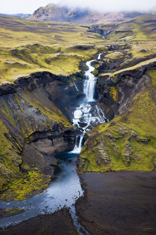 "icelandpictures:  Ófærufoss This is a waterfall in the river Ófæra that runs into the Eldgjá volcanic chasm. The Eldgjá chasm (crater in the shape of a canyon) was most likely created in an eruption in the year 934. Therefor this waterfall is quite young and still changing. Up until the 1993, there was a natural stone bridge which arched across the lower waterfall in this picture. It collapsed by itself during a flood in the river. Ófærufoss means ""the waterfall of Ófæra"" and Ófæra is the name of the river. Ófæra means ""impassible"". This picture is one of many great Iceland pictures by Thierry Hennet."