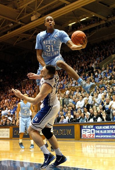 uncbball:  John Henson #31 of the North Carolina Tar Heels jumps over Miles Plumlee #21 of the Duke Blue Devils as he drives to the basket.