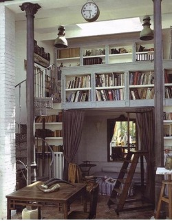 Curtained bedroom area beneath a small loft and elevated bookcase. The space looks bigger thanks to a large mirror that reflects what looks like glass doors and trees.