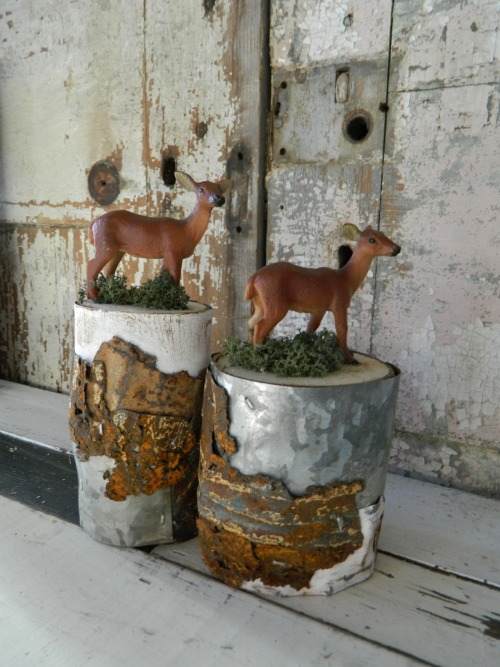 Upcycled deer figurines on top of a cut of wood covered with different scrap metal pieces.
