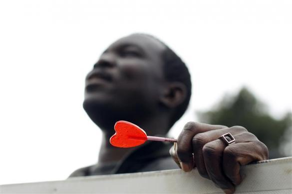 Madrid, Spain A man holds a heart-shaped lollipop during a protest outside an immigrant detention centre (via Reuters.com)