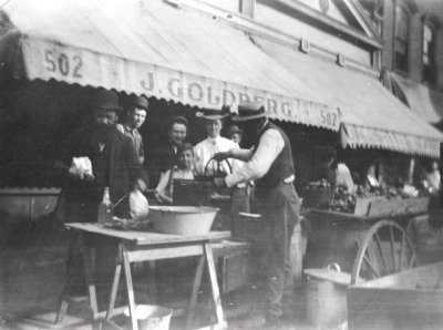 Grinding horseradish outside of Goldberg's at 502 Maxwell, c.1910, Chicago