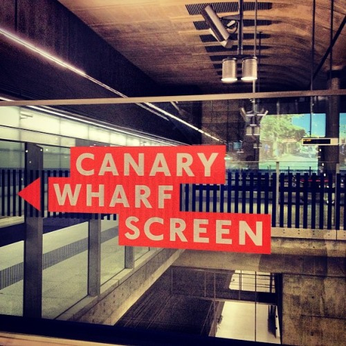 Canary Wharf Screen #sign #canarywharfscreen #art #artinstallation # artontheunderground #platformforart #londonunderground #tfl #transport #subway #projection #screen #eastwall #canarywharf #undergroundstation #easternconcourse #glasspanel #concrete #acousticdampners #speakers #lights #traintrack #down #easterninternalwall #lights #orange #white #letters #blue #jubileeline #buildingoftheyear2000 #underground #xproII #lux (Taken with Instagram at Canary Wharf Underground station)