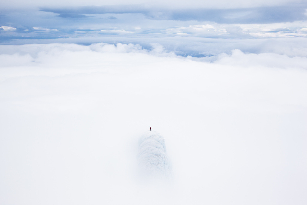 To the centre of the earth Snaefellsjokull summit, Remi Mcmurtry stands at the top of one of the two pinnacle summits. A cloud inversion whisking over the summit drew a serene heavenly atmosphere to the scene.  Photo by Will Copestake