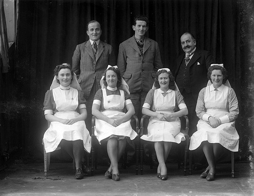 March 5, 1946 (by National Library of Ireland on The Commons)  A hospital or nursing home group taken somewhere in Waterford. The gentleman on the right is Dr Vincent White, and the other two men are Dr Hally and Mr F. Murphy, but we don't know which is which. It'd also be great to find out who the nurses were… Date: Tuesday, 5 March 1946 NLI Ref.: P_WP_4517