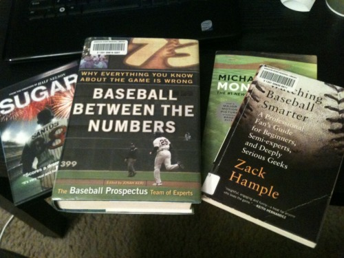 On the coffee table. Chad Harbach's 'The Art of Fielding' is on a side table along with three Eephus League official scorebooks. 2011 World Series and Eastbound & Down dvds are strewn across the floor.