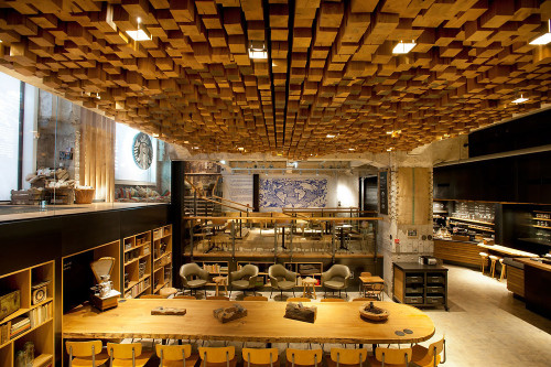 fastcompany:  Starbucks is testing a new store concept that sounds like a radical departure from the latte version you visit here in the United States.  Located in the former vault of a historic bank on Rembrandtplein, the new shop will be a showcase for sustainable interior design and slow coffee brewing, with small-batch reserve coffees and Europe's first-ever Clover, a high-end machine that brews one cup at a time. But the most radical departure is in the aesthetic: the multilevel space is awash in recycled and local materials; walls are lined with antique Delft tiles, bicycle inner tubes, and wooden gingerbread molds; repurposed Dutch oak was used to make benches, tables, and the undulating ceiling relief consisting of 1,876 pieces of individually sawn blocks. The Dutch-born Liz Muller, Starbucks concept design director, commissioned more than 35 artists and craftsmen to add their quirky touches to the 4,500-square-foot space.  Starbucks Concept Store Is A Lab For Reinventing The Brand  Whohohooooa this is super cool! I sure hope Amsterdam likes it so they build some here!