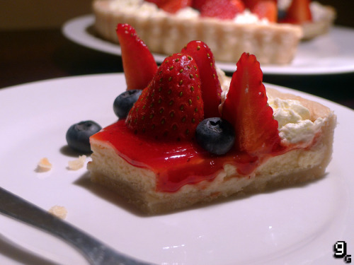 gourmetgaming:  Catherine – Strawberry Tart (Katherine)  Katherine is Vincent's long-term girlfriend who evidently has a bit of a sweet-tooth. She's rarely seen without a dessert in front of her that somehow she's been able to only take a small piece from. If I were dining at Chrono Rabbit I can assure you I'd be on my third slice of whatever strawberry covered treat was on offer. The source of Vincent's current anxieties, Katherine takes some pretty interesting and disturbing forms in his nightmares. Even her fork is seen as a threat to him, well, she is usually the one doing the killing in her dreams. I can see why Vincent is so scared; her underlying dark streak and relationship pressures are enough to make me nervous! But as long as there's desserts, everything's okay. This recipe serves 6-8. What you will need: A 9 inch (23cm) fluted tart tin with a loose base, 2 large mixing bowls, a sieve, a rolling pin, ceramic baking beans, piping bag, a small pot, cling film/saran wrap and greaseproof paper/baking parchment. For the Shortcrust Pastry: 225g / 1 ¾ Cups Plain Flour 100g / ½ Cup Butter (Chilled and Cubed) ½ Teaspoon Salt Water For the Filling: 300g / 1 ½ Cups Cream Cheese (Room Temperature) 100g / ½ Cup Fine Sugar 1 Teaspoon Vanilla Extract 2 Large Eggs (Room Temperature) 120ml / ½ Cup Soured Cream 2 Tablespoons Fine Sugar To Garnish: 175g / ½ Cup Strawberry Conserve 120ml / ½ Cup Double / Whipping Cream 2 Tablespoons Fine Sugar 16 Fresh Strawberries 18 Fresh Blueberries Making the Shortcrust Pastry: Sieve the flour into a large bowl and add the butter. Using your fingers, rub the butter into the flour until it resembles breadcrumbs. Add the salt and add water a tablespoon at a time until the mixture comes together as a dough. Wrap the dough in cling film/saran wrap and chill in the fridge for an hour before use. Meanwhile, lightly grease the tart tin and set aside. Preheat the oven to 180C/355F. Once chilled, roll out the pastry to an even thickness and line the tin. Cover with greaseproof paper/baking parchment and fill the pastry with ceramic baking beans. Place the pastry in the oven and cook for approximately 10-15 minutes. Watch the pastry to ensure it doesn't dry out or get too brown. Once it's golden and firm it's ready to come out. Remove the baking beans and greaseproof paper and leave the pastry to cool while you prepare the filling. Preparing the Filling: Turn up the oven to 220C/450F. In a large bowl, combine the cream cheese, sugar and vanilla extract. Mix well until smooth. Don't worry if it seems very liquid, this is normal. Pour the mixture into the cooled and prepared pastry, leaving a small gap at the top, and put in the oven for around 7-10 minutes or until the centre has set. Take the tart from the oven and set aside for 5 minutes to cool. Meanwhile, mix the sour cream and 2 tablespoons of sugar together. Spoon just enough of the sour cream over the top of the tart to create a thin layer. Turn the oven off and return the tart to the oven for 10-15 minutes or until the sour cream has solidified. Take the tart out and leave it to cool to room temperature before placing in the fridge for several hours or over night to chill. Making the Strawberry Tart: In a small pot, add the strawberry conserve. Warm through on a medium heat until the mixture becomes liquid. Allow it to cool for a minute before pouring a thin, even layer over the chilled tart. Place the tart back in the fridge until the strawberry conserve layer has set. Meanwhile, whisk up the double cream with the sugar and spoon into the piping bag. Pipe cream around the entire edge of the tart. Prepare your fruit for the top, check out this picture for how to arrange the blueberries and strawberries. Grab a milky coffee and enjoy the tart!  While I was trying to get a good look at the tart Katherine is eating during the game, I noticed that it actually changes a few times in one scene. It swaps between a sponge cake and the tart I've made above. I chose the tart as it was something a bit different to the previous recipes and it appears most frequently in the game. I went through 4 attempts at different varieties and combinations and then finally, I cracked it! A delicate cream-cheese layer, with caramelised sour cream topped with strawberries and blueberries is beautifully complimented by the smooth shortcrust pastry and whipped cream. Don't waste your fork on your significant other, this treat is proof there are far better things to be forking. Like this? You might also enjoy the Castlevania - Cheesecake.  This looks sooooooooo good *3*