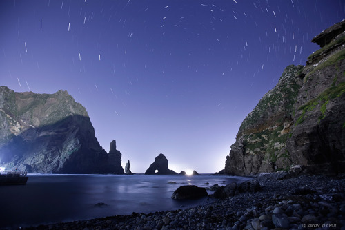 ikenbot:  Night at Dokdo by Kwon O Chul Stars trail around the north celestial pole over the coast of Dokdo island.