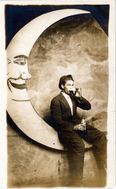 Early 20th C. arcade photograph of man drinking alcohol on a paper moon - which looks as if it's also been imbibing - by ~BostonBill~ on Flickr.