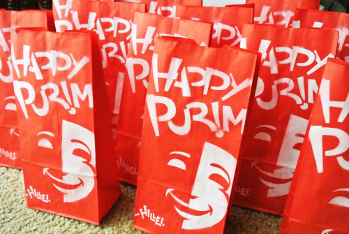 "I stenciled paper bags this morning with a ""Happy Purim"" print. It's a tradition on the the Jewish holiday of Purim (which starts Wednesday night) to give gifts of food called mishloach manot to friends. Who wants?"