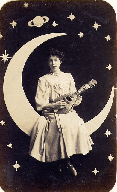 Edwardian arcade photograph of a musical young lady sitting on a paper moon - by BigalDavies on Flickr.