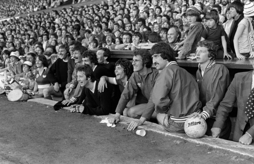 "theredsgallery:  The dugout at Anfield during the Tommy Smith Testimonial game versus a Bobby Charlton XI on May 27 1977. From left to right: Steve Heighway, John Toshack, Tommy Smith, Ian Callaghan, Terry McDermott, Jimmy Case, Kevin Keegan, Ray Clemence, David Johnson and David Fairclough. Photographer Steve Hale: ""This photograph was taken on one of those wonderfully warm late spring nights. It also just happened to be the night of Tommy Smith's testimonial match at a packed to the rafters Anfield. It also happened to take place shortly after Liverpool had won the European Cup for the first time in Rome. ""The atmosphere inside Anfield was very happy and importantly for me very relaxed. That wonderful mix gave me the opportunity and the freedom of movement to sit just in front of the bench for a short time and take this image. You can see the happiness and the relaxed feel in the faces and body language of both the players and the fans. A sheer communion of joy. The ten players in the dug out would cost an absolute fortune now individually or collectively. However, nothing could buy the collective atmosphere of happiness, pride and joy felt inside the ground  that night.""  Click here to buy a 20"" x 16"" Premium Framed version of this print from The Reds Gallery"