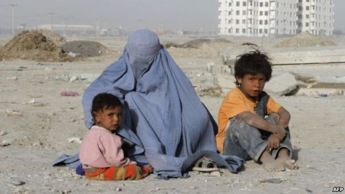A burqa-clad woman begs with her children near a newly constructed building in Kabul. Read: UN Calls On Afghan Government To Fight Violence Against Women