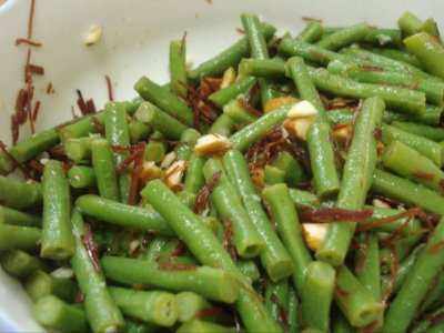 Start fresh a day with a salad. Great for diet. Green bean salad with stripes of beef and almond flakes. The original is made from Holland beans (http://t2.gstatic.com/images?q=tbn:ANd9GcRifYqIccSERug8spPK6Z-vtAFXfPYOsRvseiD6B9y124Uopx48bMUtqRDwhw), and sesame seeds. It does taste better with Holland bean and sesame seeds. Nevertheless, what kind of self-taught cook are you if you can't make pact with the market? Really. We have no Holland bean so green bean it is now :D. If you are vegan, forget the beef and try to find the sesame instead of almond. I like it that way better, lighter taste Take the ready made dry beef out and tear it to stripes. If you don't have it, marinate a piece of beef with Chinese 5 spices, peppers, garlic powder, salt for 15 minutes Now wash the bean, put in the the sauce pan with cold water and a pinch of salt. Bring to a boil. Immediately when it's boiled open the lid. Taste it (this is why my family always wonder how the food does not measure up to the ingredients I bought, lol. A cook's power) It's done when it's still crisp and does not taste raw. If you don't know how, just break open it. If you can break open it easily and the inside has darker colour than before you cook, that's a hint it's cooked. Drain the bean. Rinse in cold water, pat dry.  Ok, so the bean is ready, now boil the beef, or pour some water in the beef, covered and put in the microwave. When it's done, wait for it to cool down then stripe it.  Take the almond flake out. Now combine the bean and the beef in a bowl. Mix olive oil, sugar, rice vinegar and salt. I think sesame oil would be good, but I didn't have sesame oil so I think it's OK not to have it, I'm not sure how it would goes with the almond. The trick is to make the mixture as you want to taste the original, just be mindful of the salt if you over-salted the beef or the bean before. Pour the mixture in and toss the whole thing, sprinkle with almond flakes. Done. It's lovely to eat with crackers