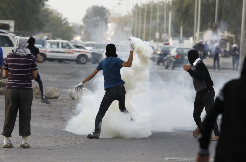 A protester through a tear gas canister back at riot police in Bahrain via Reuters
