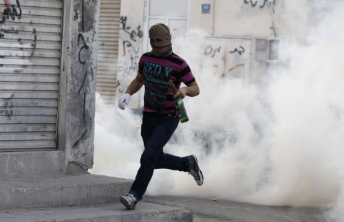 A protester runs from clouds of tear gas in Saar, Bahrain via Reuters