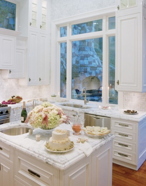 A bright and romantic white kitchen with marble countertops (via Danenberg Design)