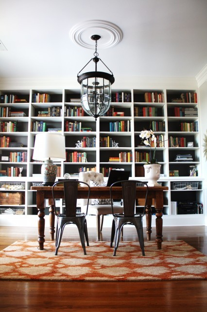 A very classy home office and library combo… the books also act as decorative pieces, bringing color to the room (via Emily A. Clark)